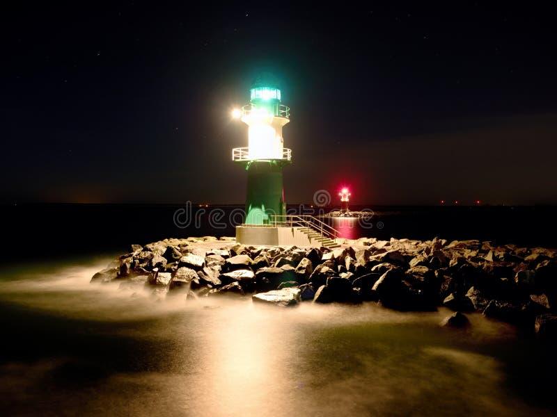 Faro verde che shinning all'estremità del pilastro pietroso nella notte scura immagini stock libere da diritti