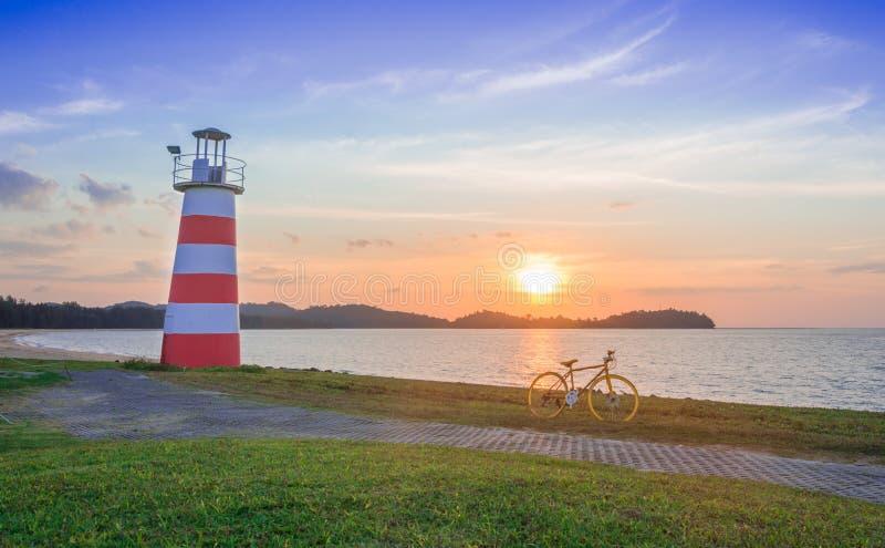 Faro y bicicleta amarilla en la puesta del sol de la playa imagenes de archivo