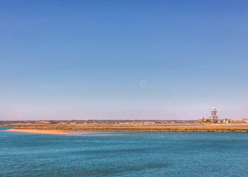 Faro y costa de Isla Cristina que miran a través de Isla Canela y de Punta del Moral, en Ayamonte, España en un día de verano pre foto de archivo libre de regalías