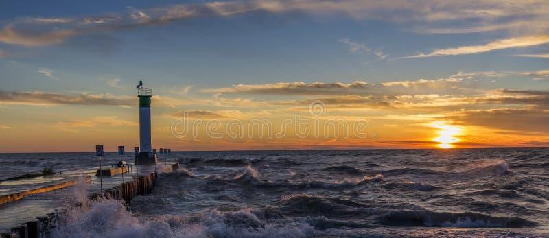 Faro y embarcadero del lago Hurón en la puesta del sol foto de archivo libre de regalías