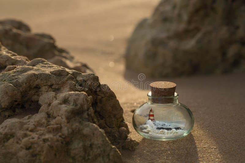 Faro y olas oceánicas dentro de la botella que se coloca en la arena entre las rocas fotos de archivo