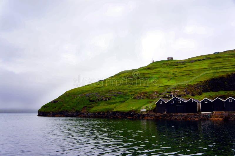 Faroe Islands boat trip, cliffs rocks houses, Denmark royalty free stock images