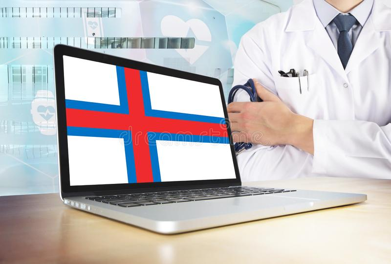 Faroe Islands healthcare system in tech theme. Flag on computer screen. Doctor standing with stethoscope in hospital. Cryptocurrency and Blockchain concept stock photo