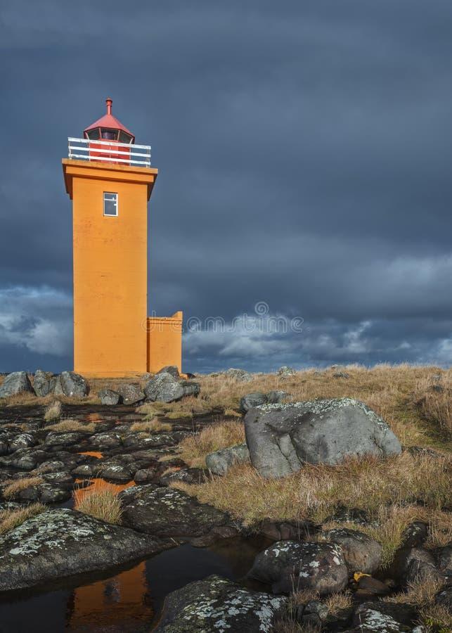 Farol alaranjado e céus tormentosos em Islândia fotos de stock