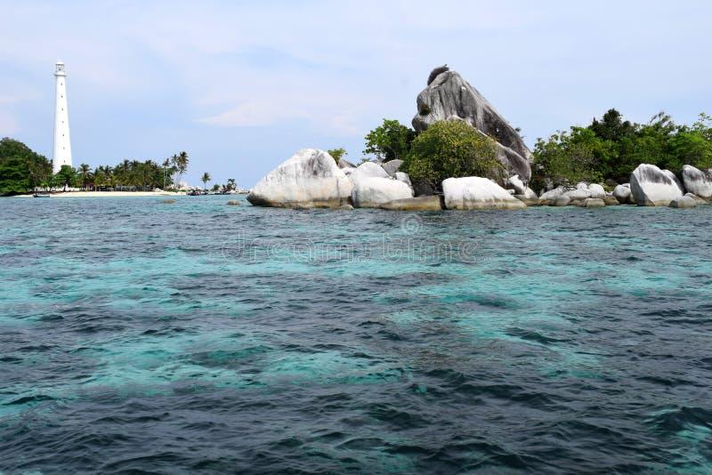 Farol branco atrás da rocha coral bonita e arbusto verde com o mar azul agradável imagens de stock