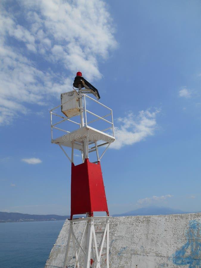 Farol branco e vermelho do metal ao lado do mar, estando na doca fotos de stock royalty free