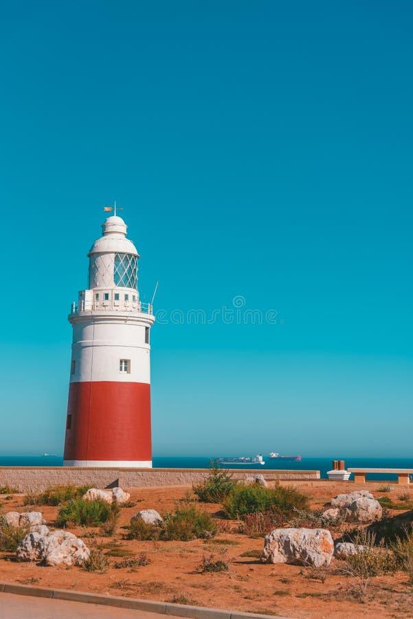 Farol branco e vermelho num mar no Reino Unido rodeado por pedras e verde imagens de stock