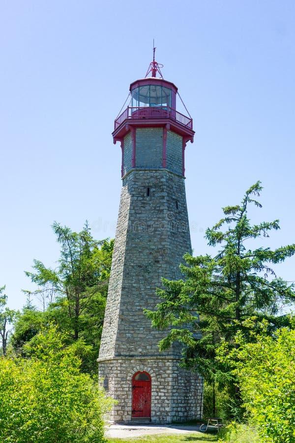 Farol de pedra alto com a porta vermelha na ilha de Toronto no parque imagens de stock