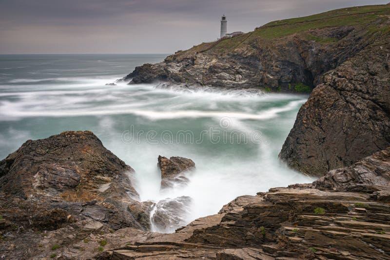 Farol de Trevose Head, no norte da Cornualha, com um céu tempestuoso e ondas a cair sobre as rochas, cria uma bela paisagem resis fotografia de stock