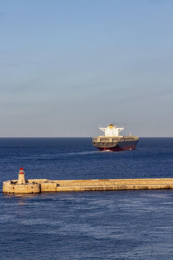 Farol do quebra-mar de Ricasoli no porto grande, Malta com um navio de recipiente fotos de stock royalty free