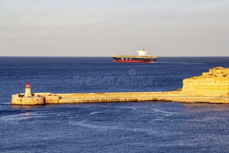 Farol do quebra-mar de Ricasoli no porto grande, Malta com um navio de recipiente imagens de stock royalty free