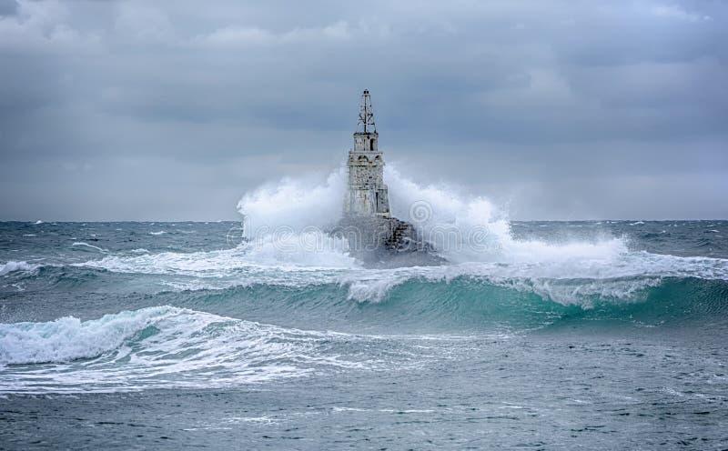 Farol e tempestade no mar e nas grandes ondas que quebram na luz do mar no porto de Ahtopol, o Mar Negro, Bulgária fotos de stock royalty free