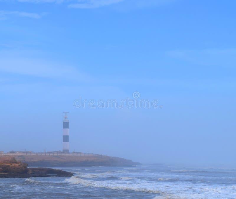 Farol em Seashore, com marmã no ar e céu azul limpo em Dwarka Point, Devbhumi Dwarka, Gujarat, Índia fotos de stock royalty free