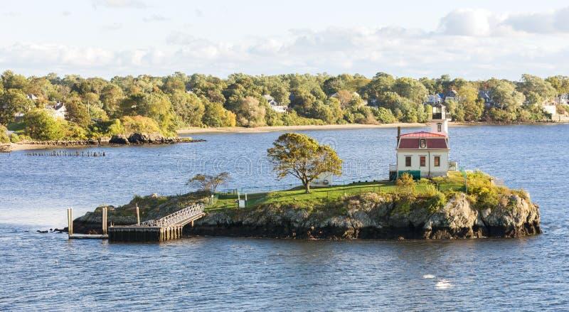 Farol em uma ilha só na baía perto da costa foto de stock