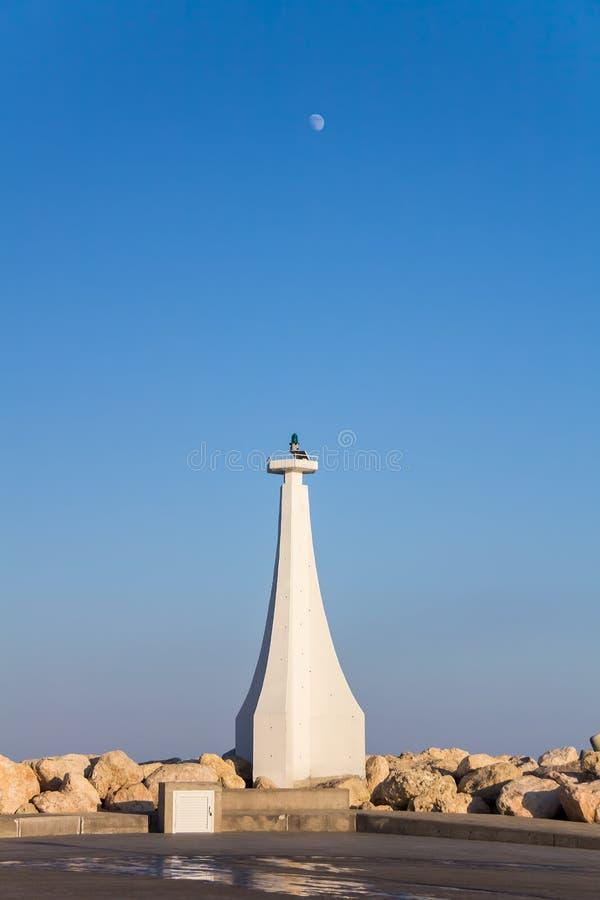 Farol na entrada a Marina On um fundo do céu azul com a lua imagens de stock