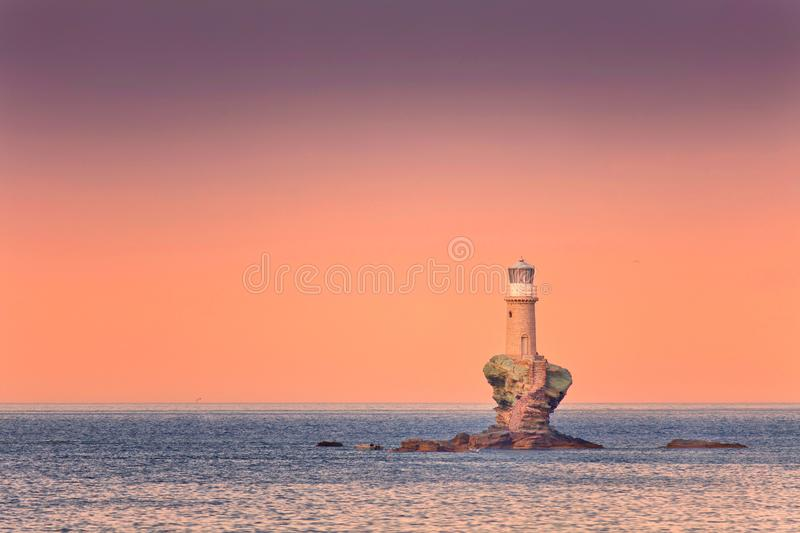Farol na rocha no por do sol fotos de stock royalty free