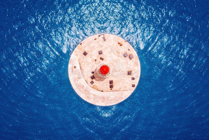 Farol vermelho contra a água azul do mar Cores do contraste Vista a?rea superior imagens de stock royalty free