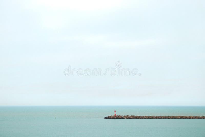 Farol vermelho no fundo do horizonte imagens de stock royalty free
