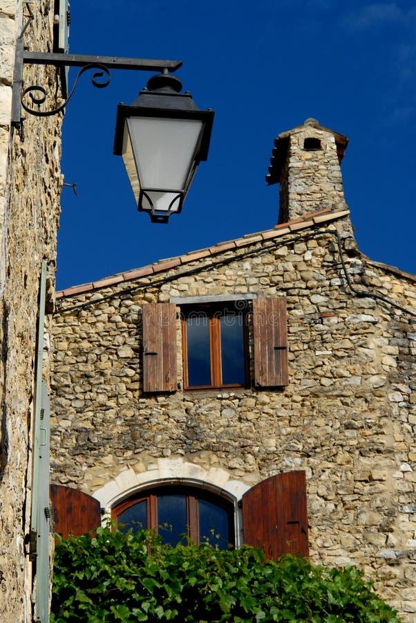 Farol y casa silueteados contra el cielo azul en Mirmande en Francia fotos de archivo