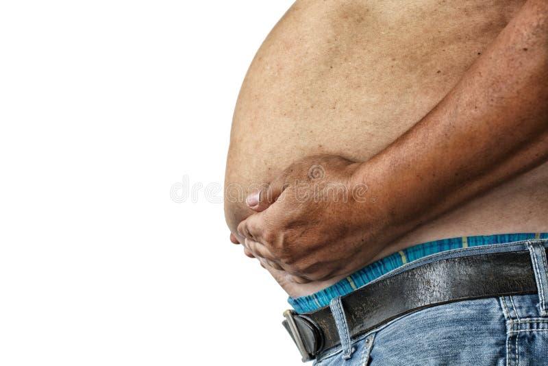Farorna av bukfett , Pressar den sjukligt feta mannen i jeans buken royaltyfri foto