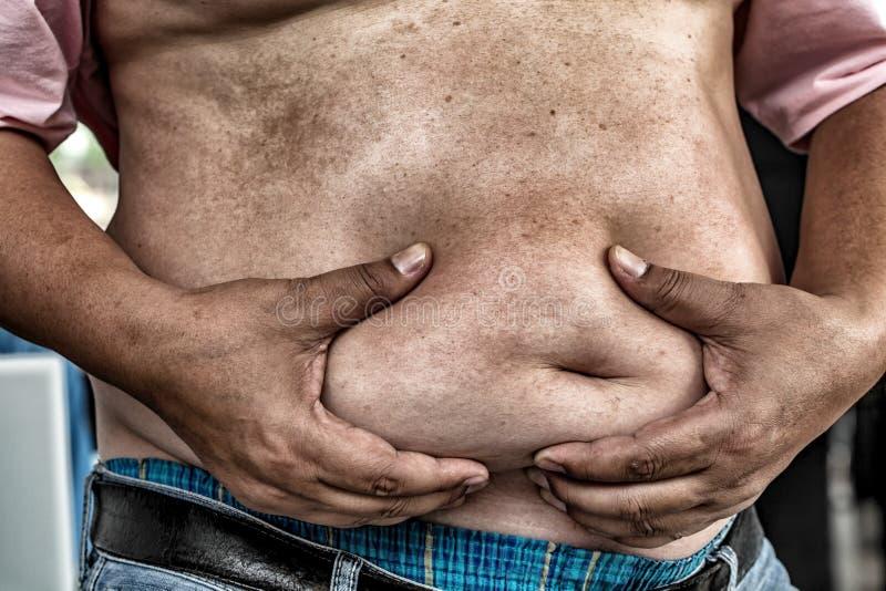Farorna av bukfett , Pressar den sjukligt feta mannen i jeans buken royaltyfri fotografi