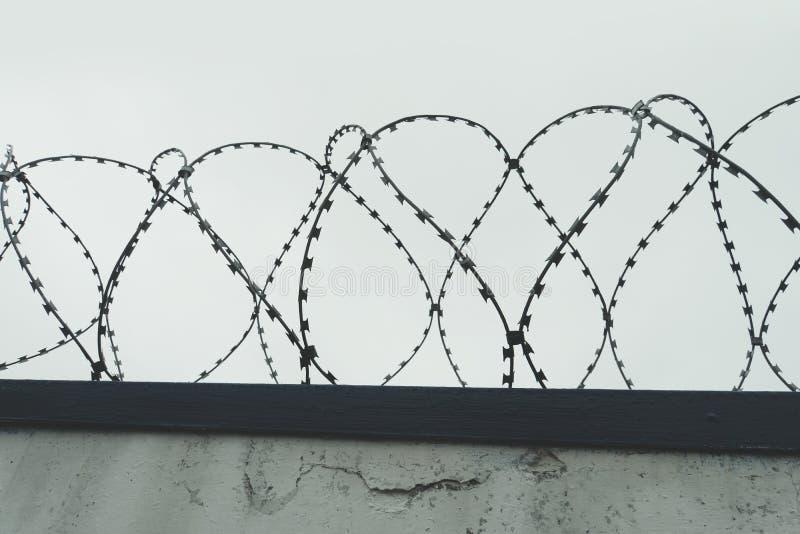 A farpa do emaranhado com céu cinzento a cerca na prisão holocaust imagem de stock