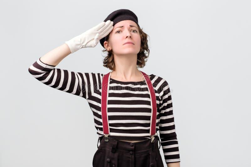 Fars f?r ung kvinna som ser kameran och att salutera arkivfoton