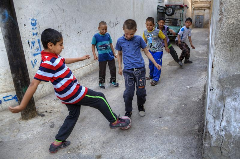 Iranian children playing football in a courtyard, Shiraz, Iran. Fars Province, Shiraz, Iran - 18 april, 2017: Iranian teenagers playing football in a courtyard royalty free stock photo