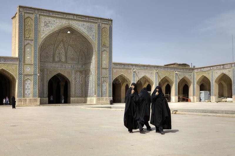 Iranian women wearing black islamic dresses in inner courtyard M