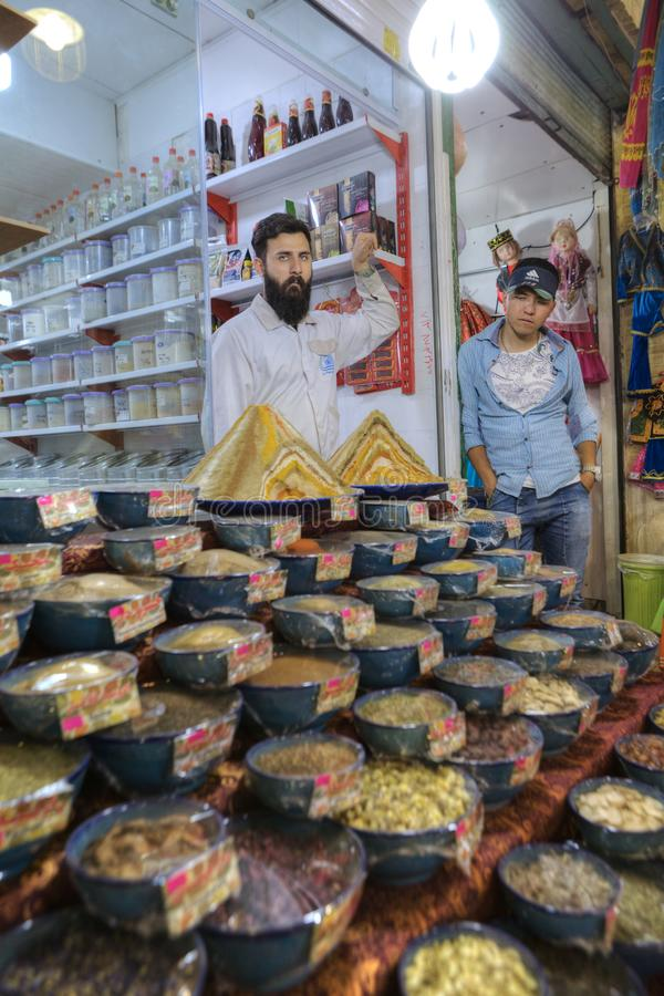 Iranian sweets traders stand near showcase of their store, Shiraz. royalty free stock images