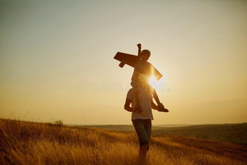 Farsa med hans son i en pilot- dräkt för ` s på solnedgången i natur royaltyfria foton