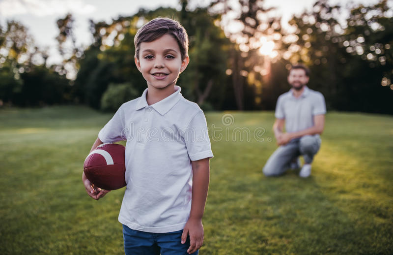 Farsa med sonen som spelar amerikansk fotboll royaltyfri bild
