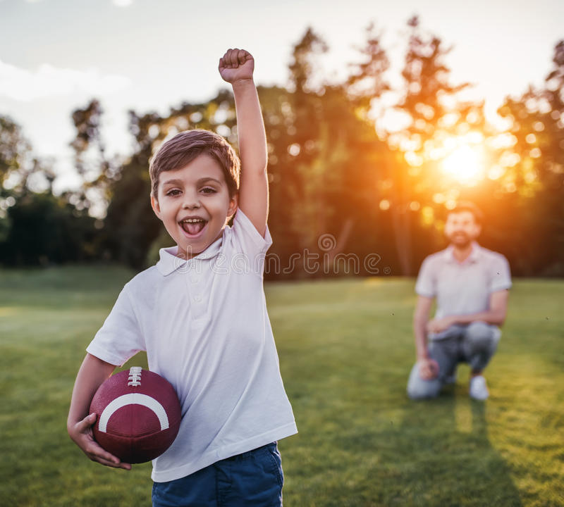 Farsa med sonen som spelar amerikansk fotboll royaltyfri foto