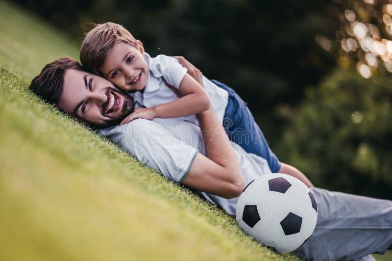 Farsa med sonen som spelar baseball royaltyfri fotografi