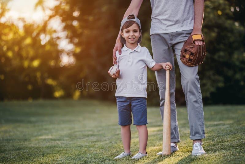 Farsa med sonen som spelar baseball royaltyfria bilder
