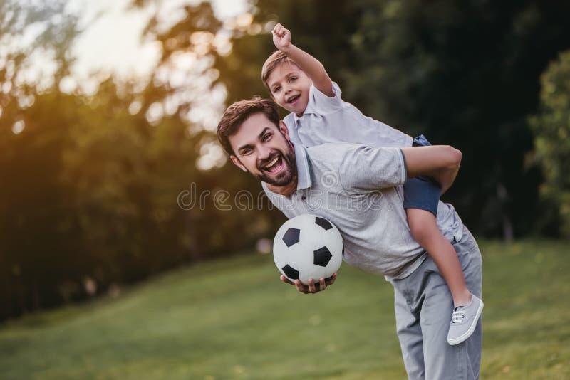 Farsa med sonen som spelar baseball arkivbilder