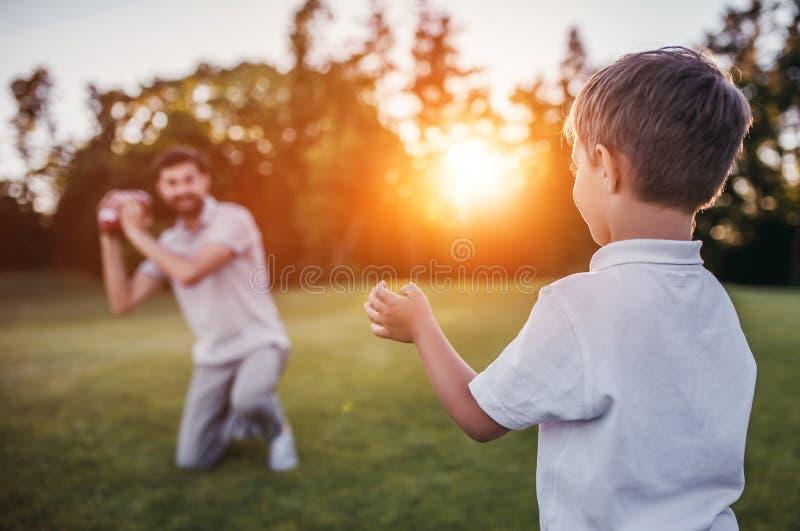 Farsa med sonen som spelar baseball royaltyfri bild
