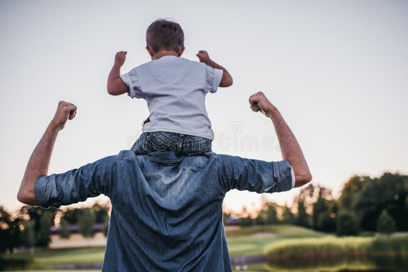 Farsa med sonen som spelar baseball royaltyfri foto