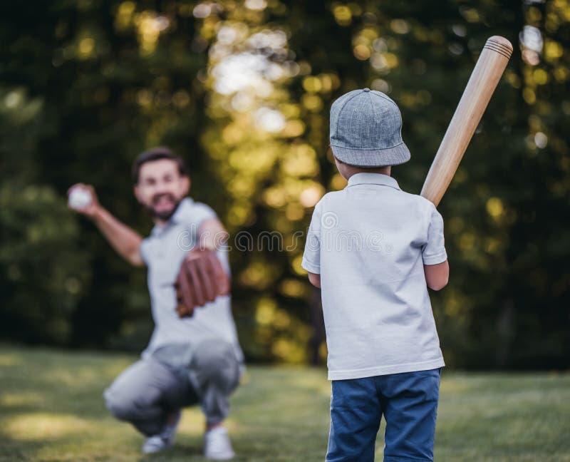 Farsa med sonen som spelar baseball arkivfoton
