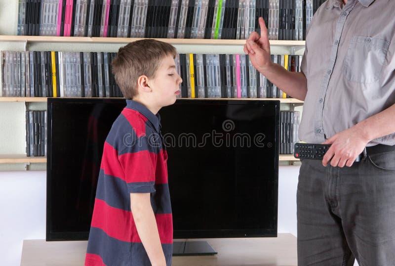 Farsa med TVfjärrkontroll som forbiding hålla ögonen på TV:N för hans son arkivbilder