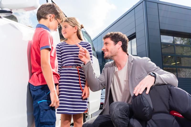 Farsa med ungar som köper familjebilen på återförsäljaren royaltyfri bild