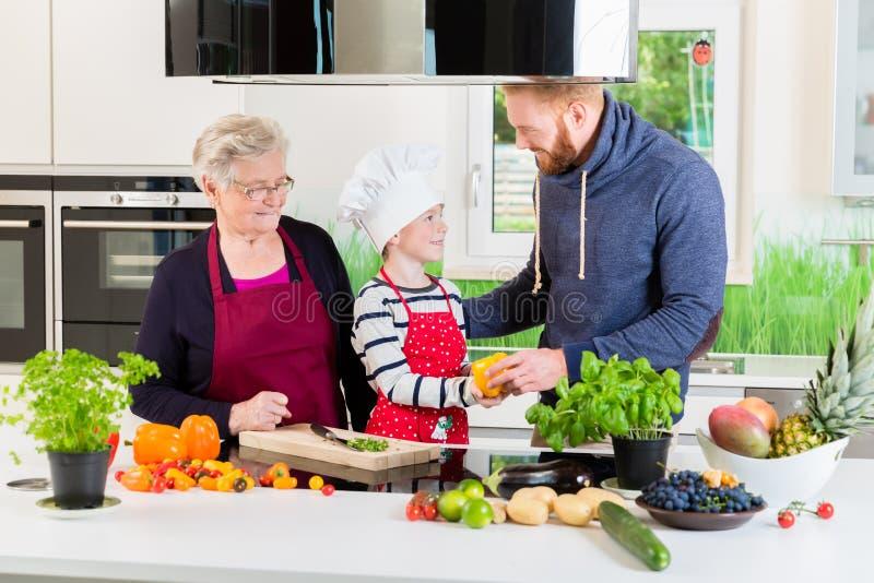 Farsa, mormor och unge som tillsammans lagar mat i kök arkivbild