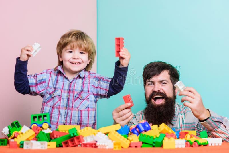 Farsa och barn att bygga plast- kvarter lycklig familj Barns utveckling och uppfostran Betydelse av att spela tillsammans farsa royaltyfria foton