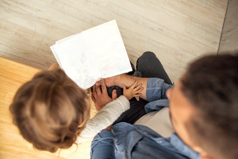 Farsa och dotter som hemma läser en bok fotografering för bildbyråer