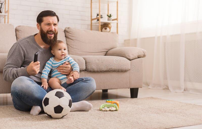 Farsa och hans hållande ögonen på fotboll för son hemma royaltyfri bild