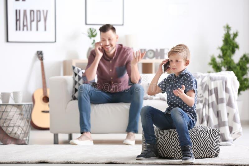 Farsa och hans lilla son som hemma talar på mobiltelefoner arkivfoton