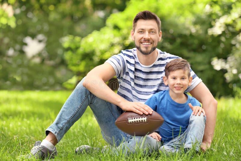 Farsa och son med rugbybollen royaltyfri fotografi