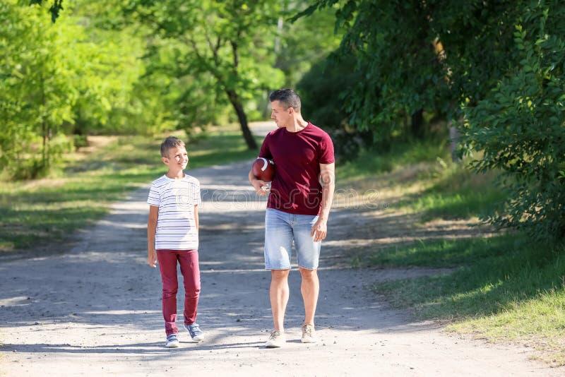 Farsa och son med rugbybollen utomhus arkivbilder