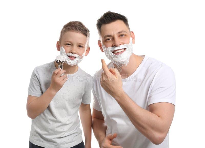 Farsa och son som applicerar raka skum royaltyfri foto