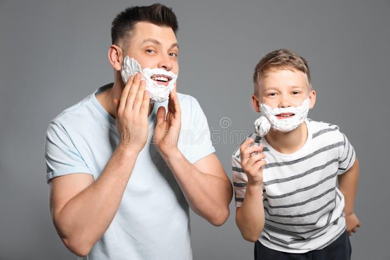 Farsa och son som applicerar raka skum arkivfoton